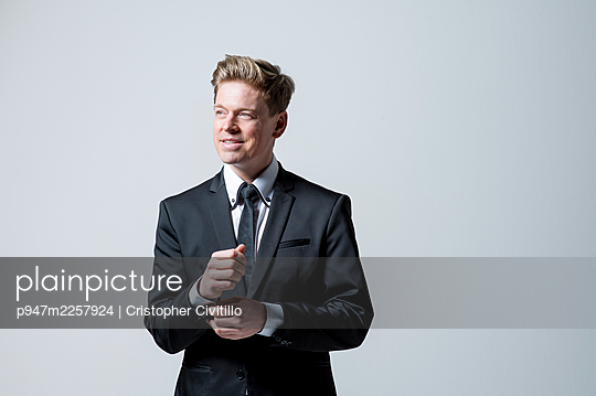 Businessman fastening cufflinks, portrait - p947m2257924 by Cristopher Civitillo