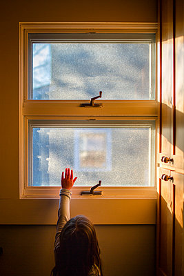 A small child reaches her hand up to sunlight streaming through window - p1166m2095981 by Cavan Images