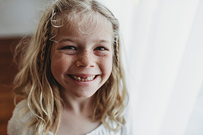 Portrait of young freckled smiling girl missing tooth - p1166m2130901 by Cavan Images