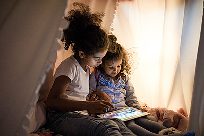 Two sisters sitting in dark children's room, looking at digital tablet - p300m1535774 by Robijn Page