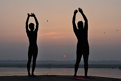India, Uttar Pradesh, Varanasi, Silhouette of two men doing sunrise ritual at River Ganges - p300m878613 by Jochen Schlenker