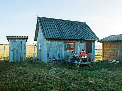 People having meal in front of wooden house - p312m1229339 by Michael Jonsson
