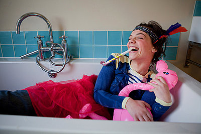 Young woman in bath, wearing costume and blowing party blower - p92411804f by Ariel Kay