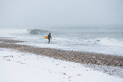 Man going surfing during winter snow - p1166m2177108 by Cavan Images
