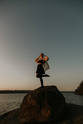 Girl dancing on a rock at sunset - p1507m2263131 by Emma Grann