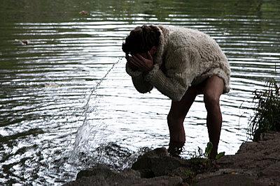 Junger Mann am Fluß benetzt Gesicht mit Wasser - p1650m2231573 von Hanna Sachau