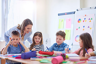 Smiling teacher helping pupils with their tasks in class - p300m1587527 by gpointstudio