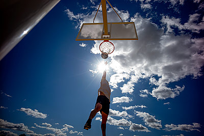 Man playing basketball, dunking against the sun - p300m2144255 by Oscar Carrascosa Martinez