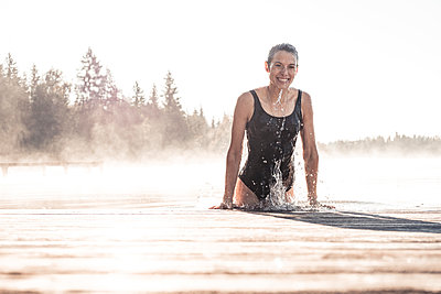 Happy woman wearing black swimsuit bathing in a lake at morning mist - p300m2156884 von Wilfried Feder
