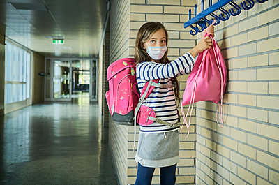 Girl wearing mask in school hanging up pouch - p300m2197944 by Dirk Kittelberger