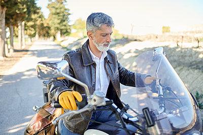 Mature man holding handlebar while checking controls of motorcycle during road trip - p300m2275591 by Kiko Jimenez