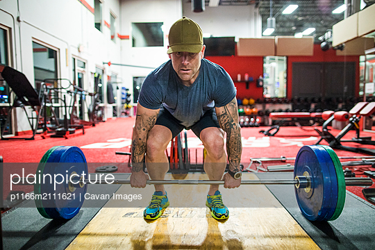 Man ready for deadlift exercise using a barbell in gym - p1166m2111621 by Cavan Images