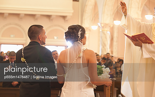 Hispanic bride and groom in wedding ceremony - p555m1478487 by Sollina Images