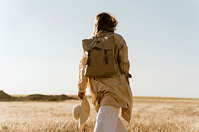 Rear view of female traveller with backpack on meadow - p300m2114112 by Eloisa Ramos