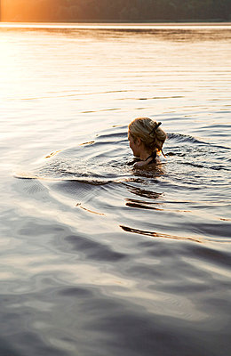 Woman swimming in a lake - p4240266 by Justin Winz