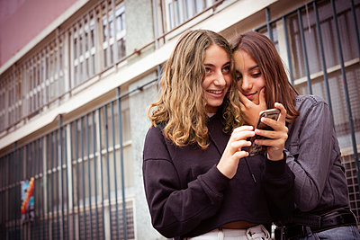 Friends using smartphone outdoors - p623m2151654 by Frederic Cirou