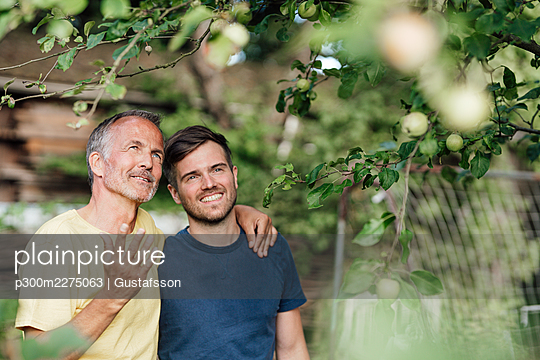 Father with arm around son discussing while looking at tree in backyard - p300m2275063 by Gustafsson