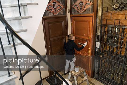 Painter painting door in apartment building - p352m2121426 by Folio Images