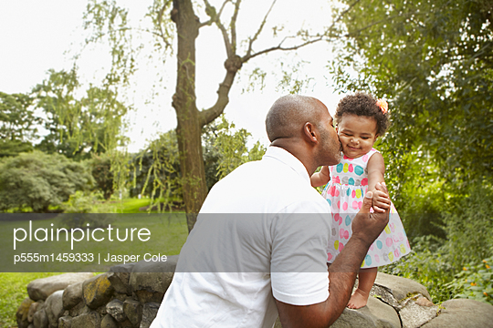 Mixed race father kissing daughter in park