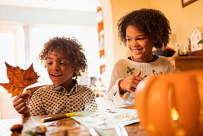 Happy brother and sister with autumn leaf doing crafts at table - p1023m2187698 by Sam Edwards