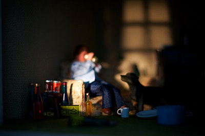 Man (doll) drinking from tin with dog - p1072m857577 by Sarah Smith