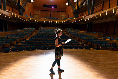 Female performer reviewing notes on stage in empty auditorium - p1192m2123234 by Hero Images