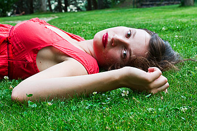 Woman lying on grass - p1445m2129076 by Eugenia Kyriakopoulou
