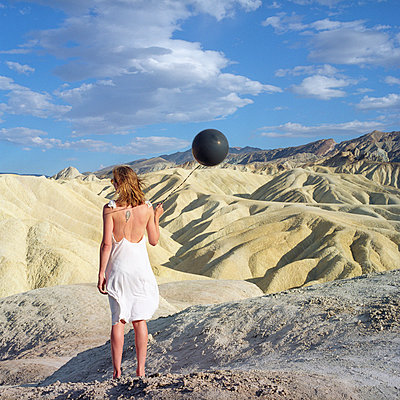 Woman Holding a black ballon at Zabriskie Point - p1610m2181496 by myriam tirler