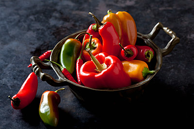 Bowl of various organic bell peppers and chili peppers on dark ground - p300m1505727 by Dieter Heinemann