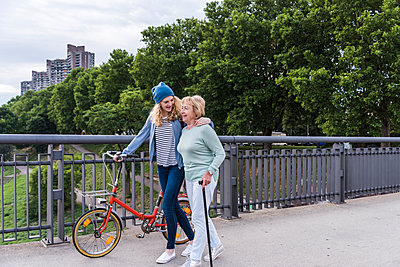 Grandmother and granddaughter strolling on a bridge - p300m2013165 by Uwe Umstätter