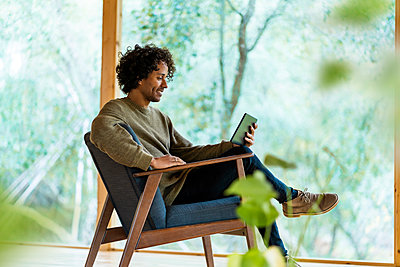 Young man using digital tablet while sitting on armchair by window at front yard - p300m2267274 by Steve Brookland