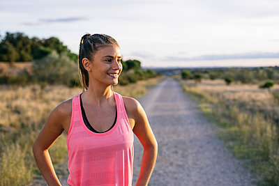 Smiling woman looking away while standing on country road during sunset - p300m2273510 by Andrés Benitez