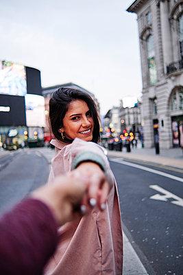 Happy woman holding hand of boyfriend on street in city - p300m2273676 by Angel Santana Garcia