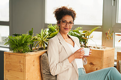 Confident businesswoman with coffee cup sitting at office - p300m2281432 by Annika List