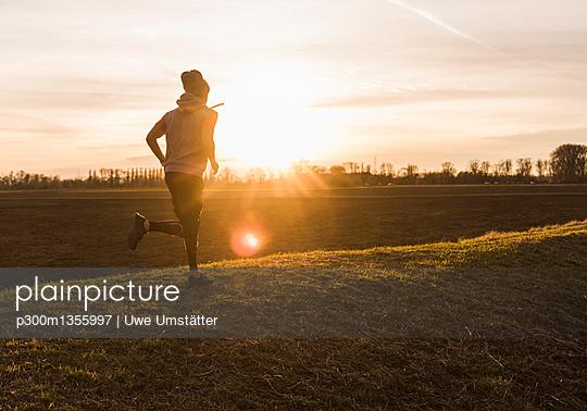 Man running in rural landscape at sunset - p300m1355997 by Uwe Umstätter