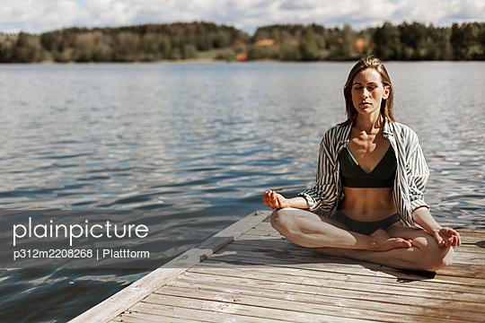 Woman meditating on jetty - p312m2208268 by Plattform
