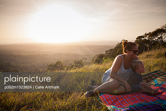 Mother and son sitting in a field in Kenya - p352m1523824 by Calle Artmark