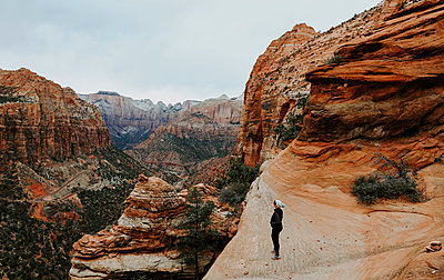 Full length of female hiker standing on rock formation at Zion National Park - p1166m1560824 by Cavan Images