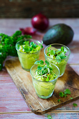 Glasses of avocado cream with chili flakes, cress and parsley - p300m1568181 von Kai Schwabe