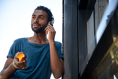 Handsome man holding apple while talking on smart phone in balcony - p300m2281518 by Buero Monaco