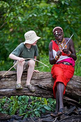 One Wilderness Trails' Laikipiak Maasai guides shows child how to sharpen an arrow - p6521164 by John Warburton-Lee