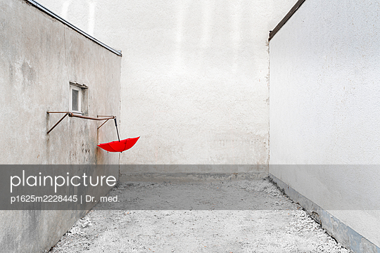 Red umbrella in a backyard - p1625m2228445 by Dr. med.