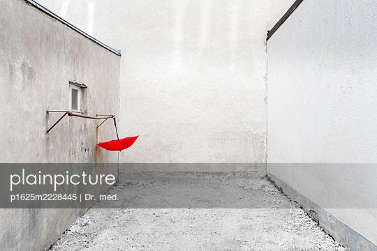 Roter Regenschirm in einem Hinterhof - p1625m2228445 von Dr. med.