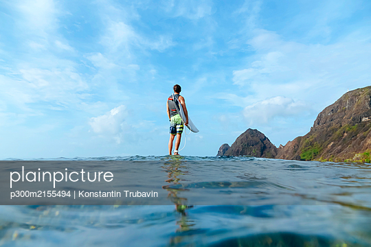 Surfer holding his surf board, standing on stone, Sumbawa island, Indonesia, over-under image - p300m2155494 by Konstantin Trubavin