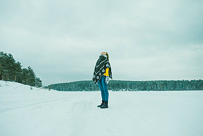 Beautiful girl standing on the ice in warm clothes - p1166m2136309 by Cavan Images