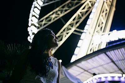 Mid adult woman smiling while looking at illuminated ferris wheel - p300m2281309 by Andrés Benitez