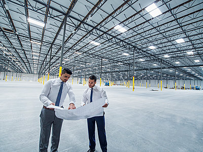 Architects examining blueprint in empty warehouse - p555m1305132 by Erik Isakson