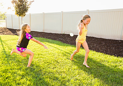 Caucasian girl throwing water balloons in backyard - p555m1415631 by Mike Kemp