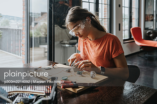 teenage girl tinkering with soldering iron at home - p300m2214092 by Mareen Fischinger