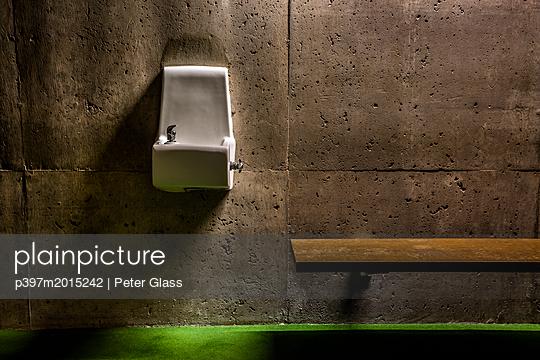 Trinkwasserbrunnen und Holzbank an einer Betonmauer - p397m2015242 von Peter Glass